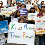 Group of adults and children protesting family separations at an outdoor demonstration