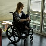 Woman in wheelchair looking plaintively out window